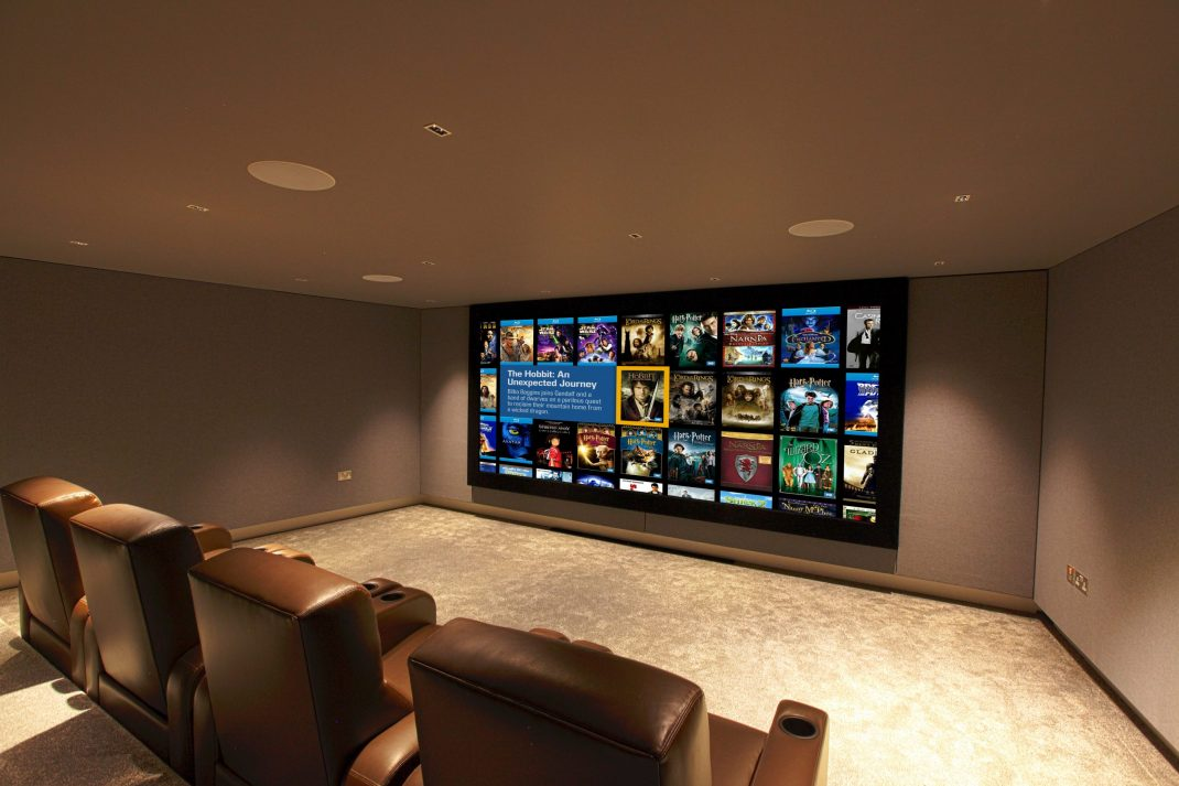 Immersive home cinema, looking at screen from rear right. Shows Fortress seating and Kaleidescape image.