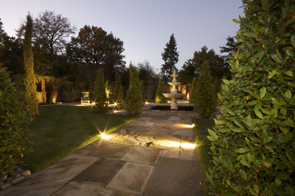 Garden with outside lighting, low level lights and accent light on fountain.