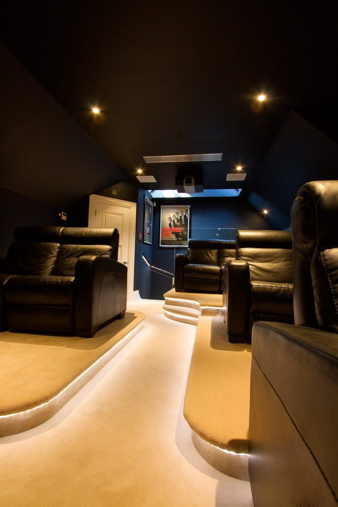 Image shows rear of home cinema with projector mounted on ceiling.