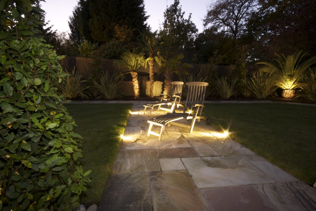Kent home with Outside Lighting, shows palm trees with uplights and deckchairs with path lights.