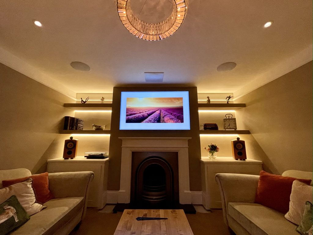Mood lighting in media room, TV above fireplace, speakers and pendant.