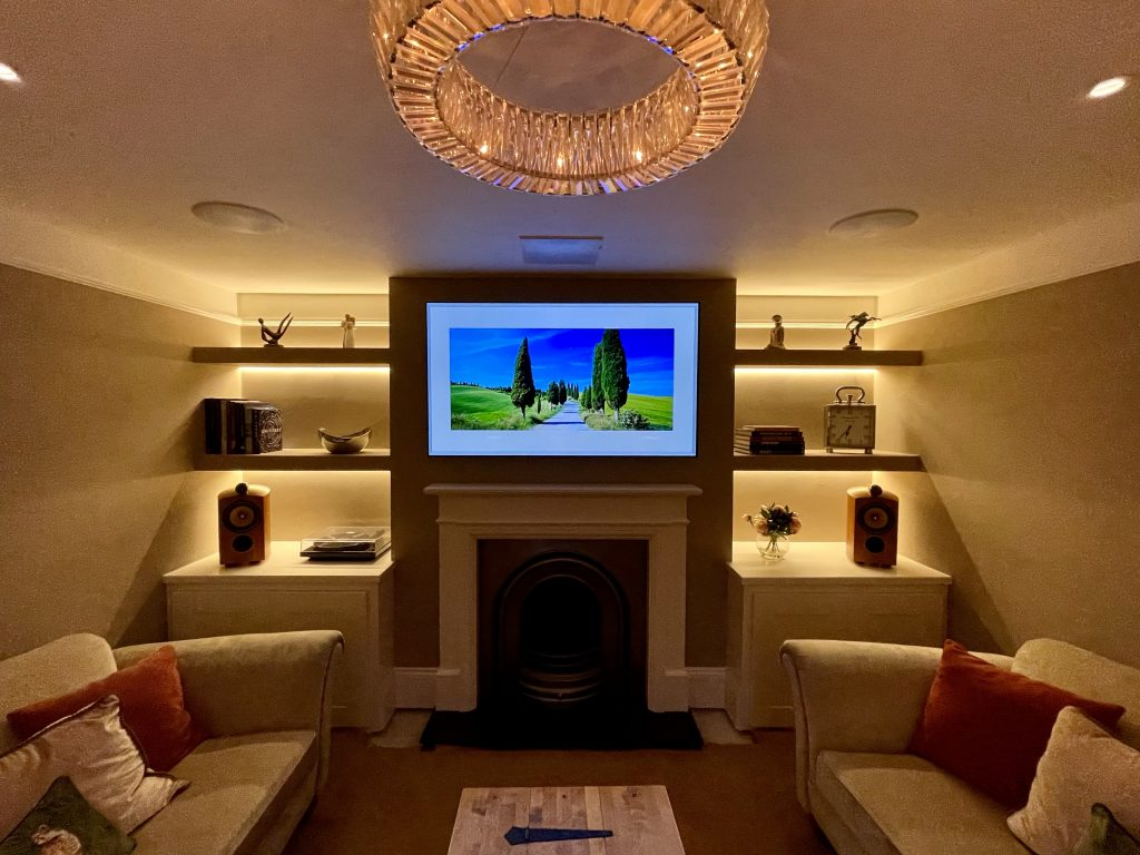 Lutron lighting in home cinema media room, with TV above fireplace and in ceiling speakers