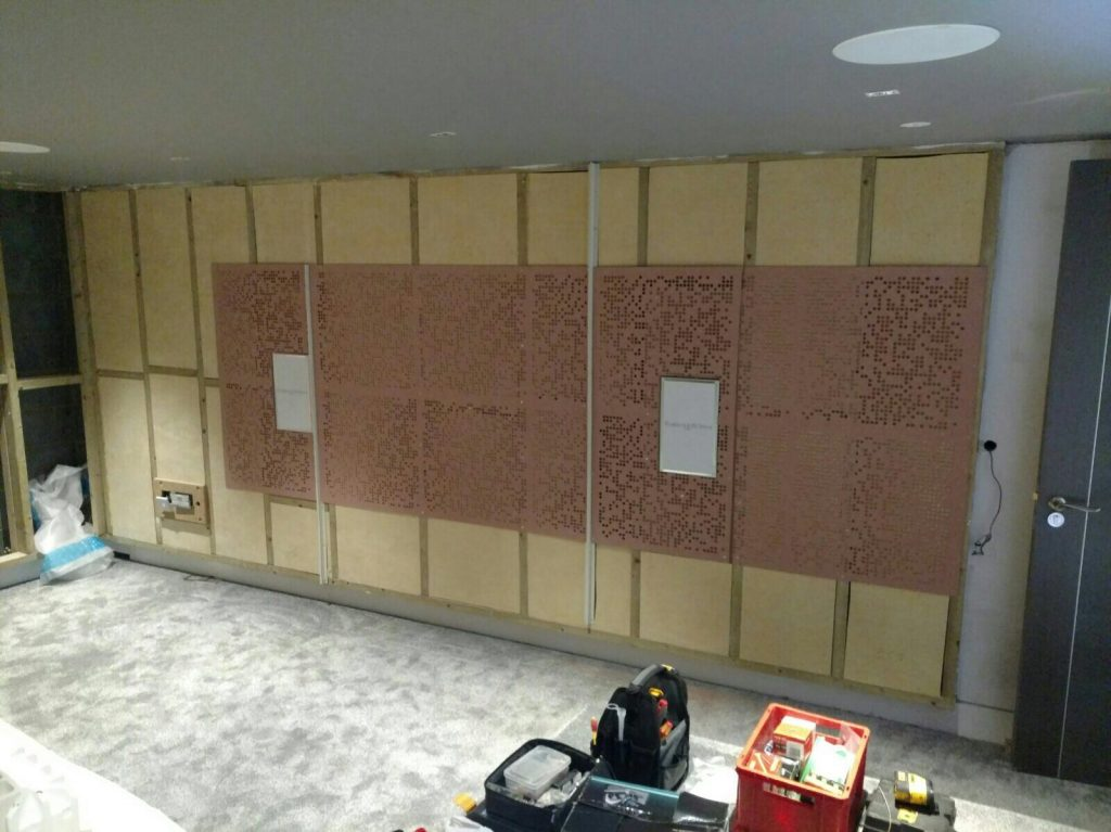 Shows wall of cinema during installation of acoustic treatment. Also two in-wall speakers and an in-ceiling speaker.