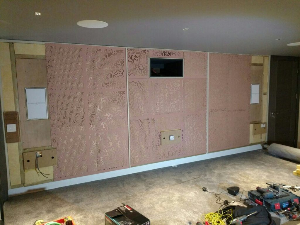 Image shows rear wall of home cinema, with acoustic treatment and aperture for projector.