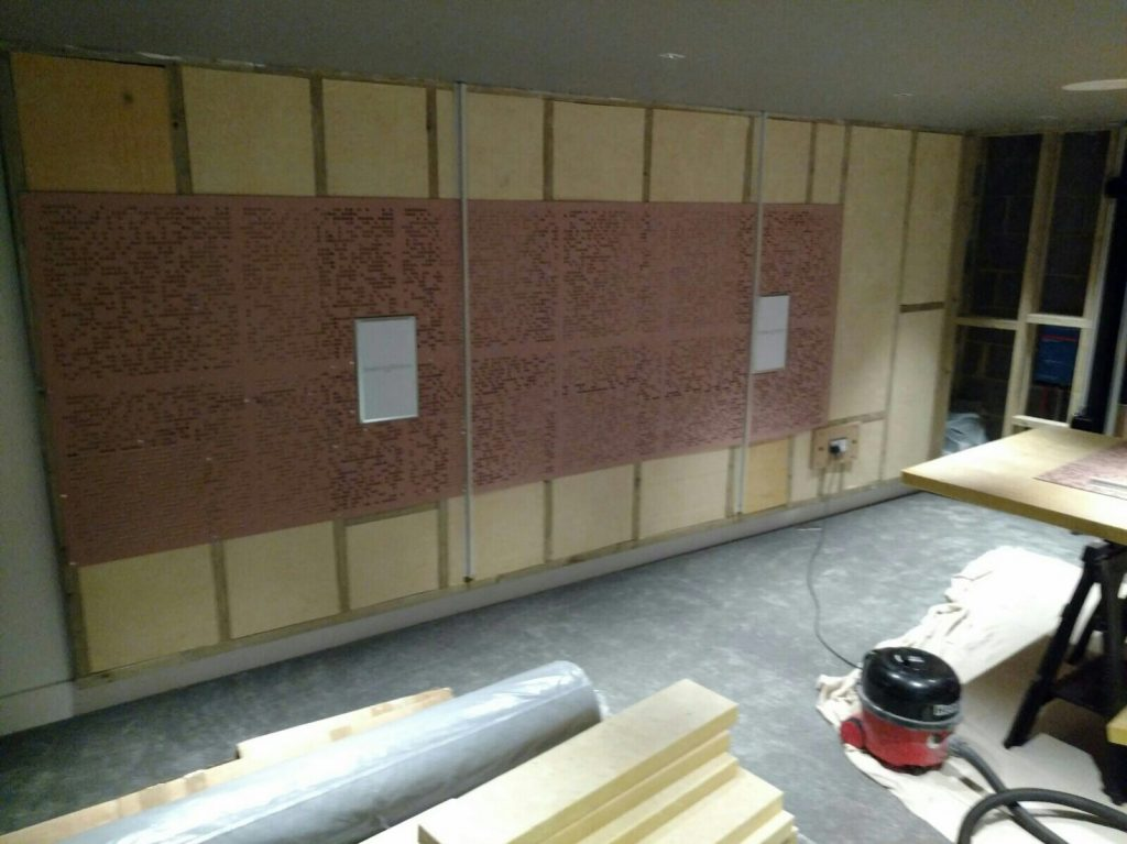 Side wall with in-wall loudspeakers and acoustic treatments.