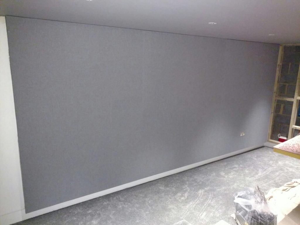 Shows grey stretched fabric covering the side wall and hiding the speaker and acoustic treatment.