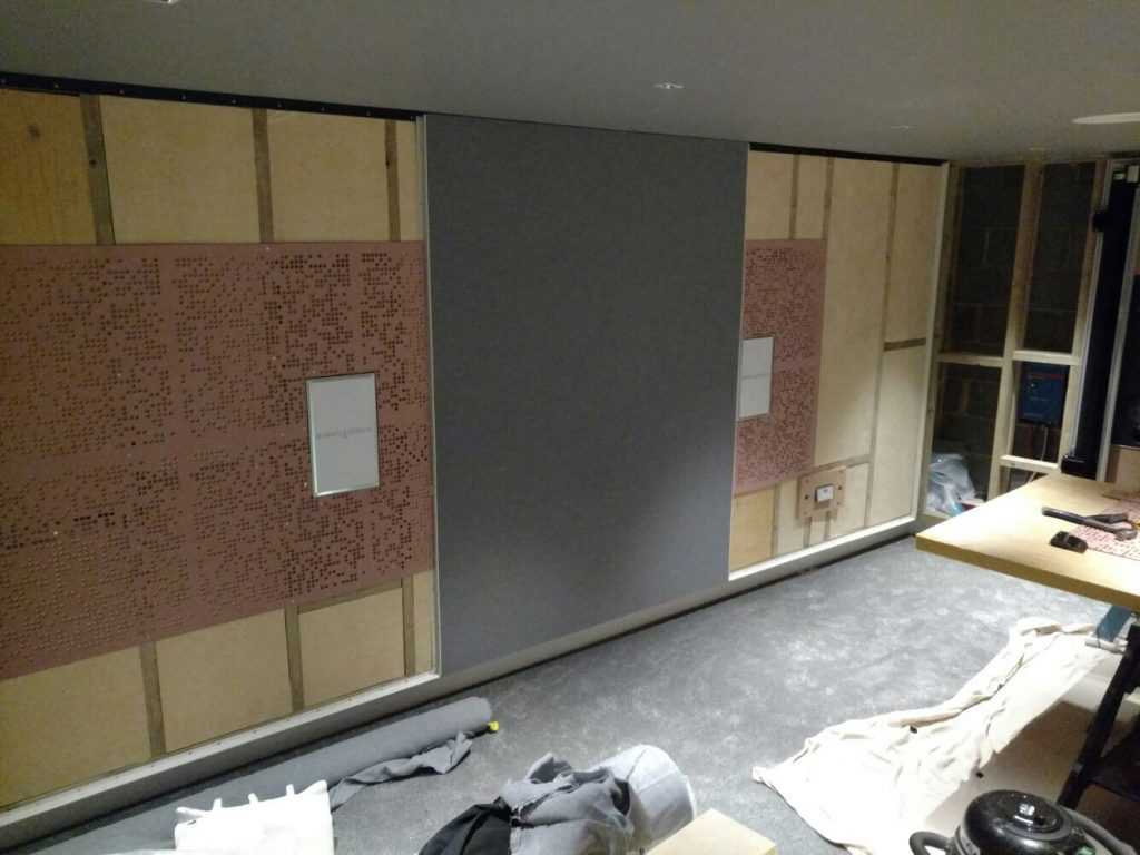 Image shows the home cinema side wall and acoustic treatment, with stretched fabric being installed.